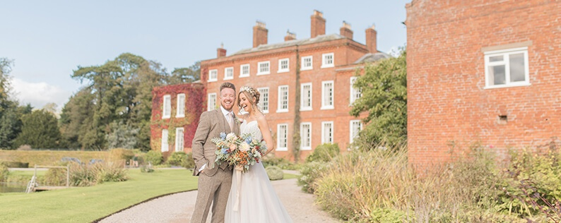 The happy couple pose for a wedding photo at Delbury Hall wedding venue in Shropshire