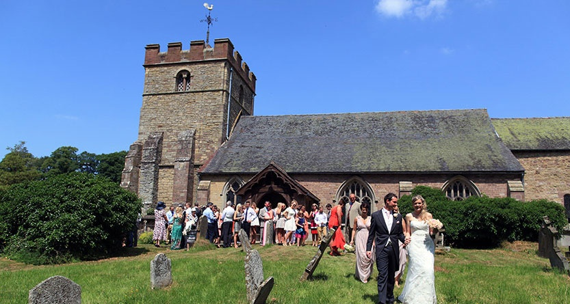 Bride, groom and guests in front of St Peter's Church wedding venue Worcester